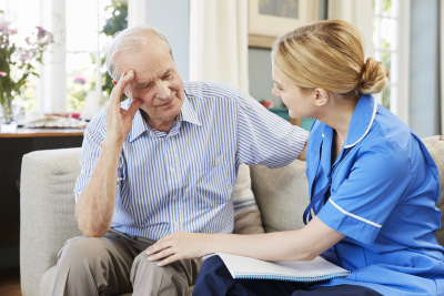 female caregiver having conversation with senior man