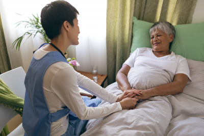 female caregiver taking care and holding the hands of senior woman