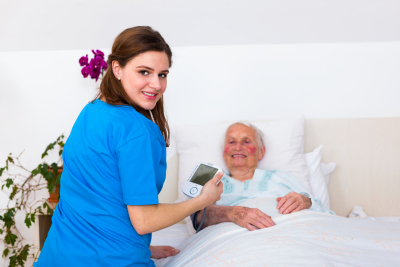 caregiver measuring senior woman's blood pressure