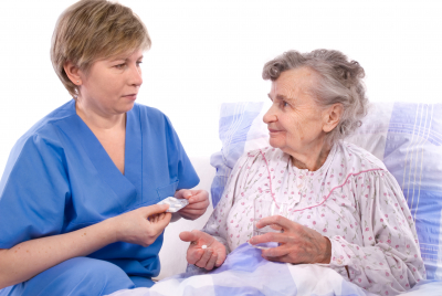 caregiver giving medicine to senior woman